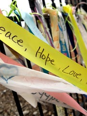 In this Dec. 9, 2014, photo, brightly colored ribbons flutter from a wrought-iron fence along the a main thoroughfare in Ferguson, Mo. Up and down South Florissant Road, paint has transformed the sheets of plywood covering windows broken during last month's rioting into works of art.  (AP Photo/Jeff Roberson)