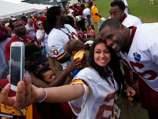 A fan takes a selfie with Washington Redskins fullback Darrel Young after practice at the team's NFL football training facility, Saturday, July 26, 2014 in Richmond, Va. (AP Photo/Alex Brandon)