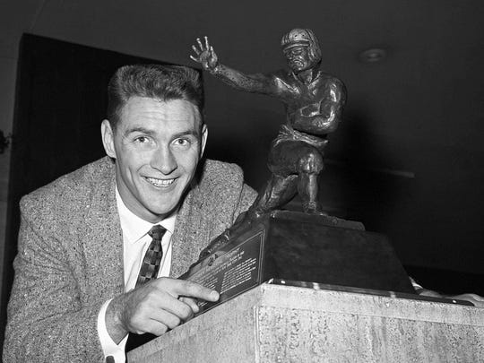 This Dec. 8, 1959 file photo shows Billy Cannon posing with the Heisman Trophy.