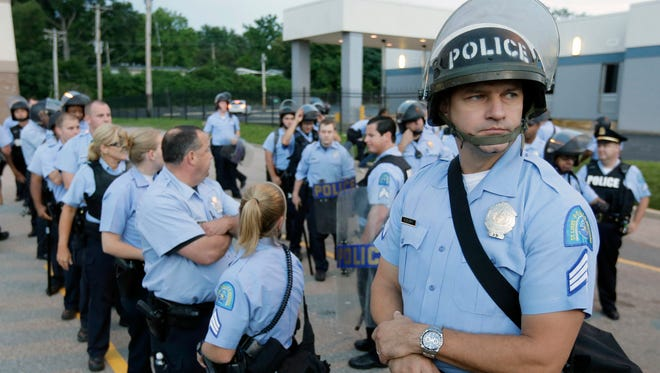 FILE - In this Aug. 16, 2014 file photo, police in riot gear prepare to take up positions as people protest the police shooting death of Michael Brown in Ferguson, Mo. Missouri and St. Louis-area economic development groups and lenders are committing $1 million in support to businesses affected by the unrest in Ferguson that followed the shooting death of an unarmed black 18-year-old by a white police officer, Gov. Jay Nixon said Thursday, Aug. 28, 2014. (AP Photo/Charlie Riedel, file)