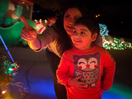 Maggie Loya points out Christmas decorations to her daughter, Jae Burunda, 3, at Dan Wasser's home. Wasser spent three weeks, 60 hours a week, stringing more than 90,000 lights over his house for Christmas.
