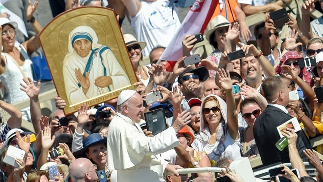 Pope Francis waves to faithful as he leaves after a Holy Mass and the canonization of Mother Teresa of Kolkata, on St. Peter's Square in the Vatican, on Sept. 4, 2016.  Mother Teresa, the nun whose work with the dying and destitute of Kolkata made her a global icon of Christian charity, was made a saint on Sept. 4, 2016. Her elevation to Roman Catholicism's celestial pantheon came in a Mass presided over by Pope Francis in the presence of 100,000 pilgrims.