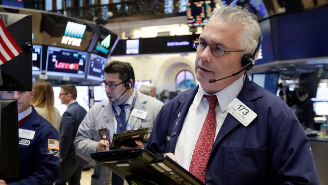 Trader Frank O'Connell, right, works on the floor of the New York Stock Exchange, Monday, Nov. 21, 2016.