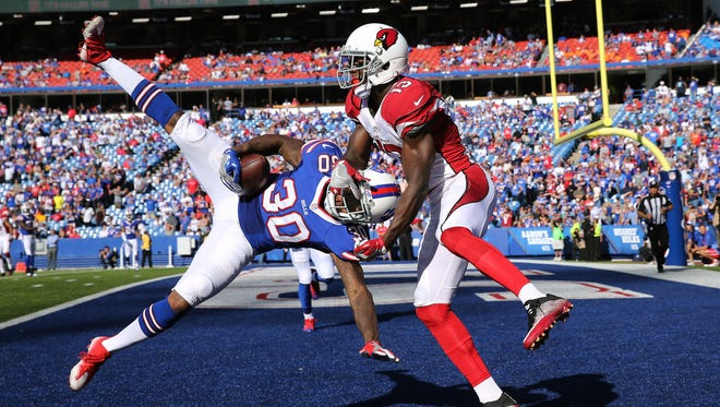 Buffalo cornerback Corey White steps in front of Arizona receiver Jaron Brown to intercept this pass in the end zone and seal a 33-18 Bills win.