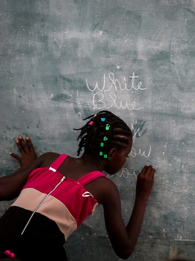 A Haitian student writes in English on the chalkboard