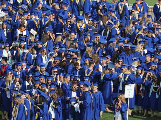 Students gather before the University of Delaware commencement ceremonies at Delaware Stadium on Saturday.
