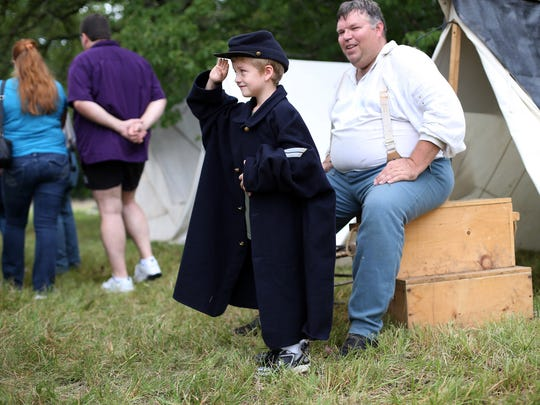 Xavier Mathewson, of Cub Scout Pack 1180 in Woodbury, tries on Robert Spegal's uniform during an artillery encampment and battery firing program Saturday, July 19, 2014 at Stones River National Battlefield.