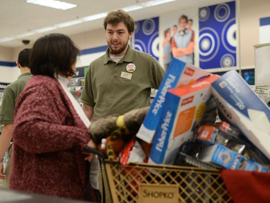 Shopko employee Jacob Meyer answers a question for a Black Friday shopper in the electronics section of a Green Bay Shopko store on Friday, Nov. 28, 2014.