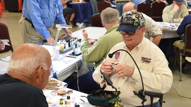 Fred DuPre of Flippin answers questions while he ties a fly during last year's Sowbug Roundup. The North Arkansas Fly Fishers will present the 21st annual Sowbug Round this Thursday through Saturday at the Baxter County Fairgrounds.
