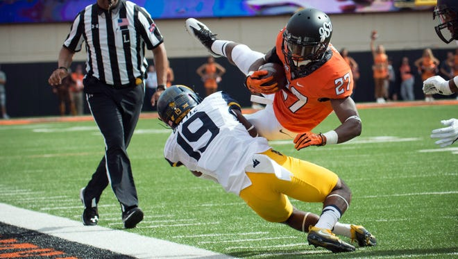 Oklahoma State Cowboys running back Justice Hill (27) tackled by West Virginia Mountaineers cornerback Elijah Battle (19).