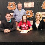 Maddie Miller sits with her coach and parents as she's signs on the dotted line to play tennis for Saginaw Valley State next season.