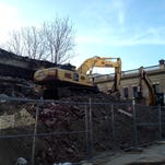 Piles of rubble remain Monday where buildings were demolished on South Third Street in downtown Louisville.