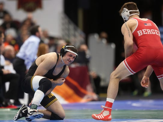 Iowa's Michael Kemerer clutches his arm while wrestling
