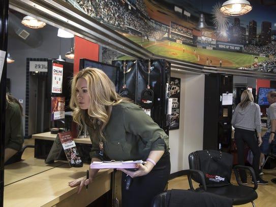 Cosmetology investigator Amber Bingham checks a license