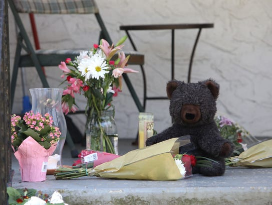 A memorial with a teddy bear, candles and flowers on