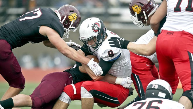 St. Cloud State quarterback Nate Meyer (8) is sacked by University of Minnesota-Duluth linebackers Brent Stiglich (59) and Mark Nahorniak (37) during Saturday's game at Malosky Stadium in Duluth.