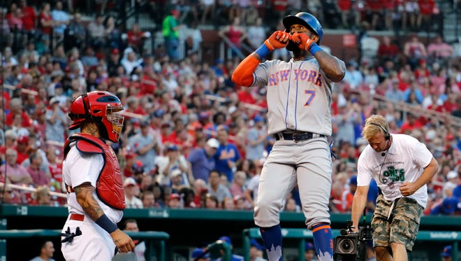 New York Mets' Jose Reyes (7) celebrates as he scores past St. Louis Cardinals catcher Yadier Molina after hitting a solo home run during the second inning of a baseball game Friday, July 7, 2017, in St. Louis.