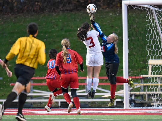 Apollo goaltender Anna Carlson leaps to block a shot during the first half of the Thursday, Oct. 27, game against Benilde-St. Margarets at Husky Stadium in St. Cloud.