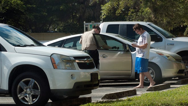 A Lee County Sheriff's Offfice deputy checks a car for prints. The vehicle was one of several that was broken into Wednesday morning.