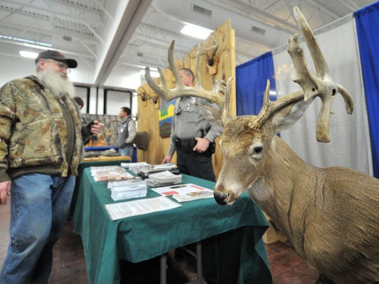 Exhibitors talk with people visit Sunday's Wisconsin Deer Classic and Hunting Expo at The Patriot Center in Rothschild.
