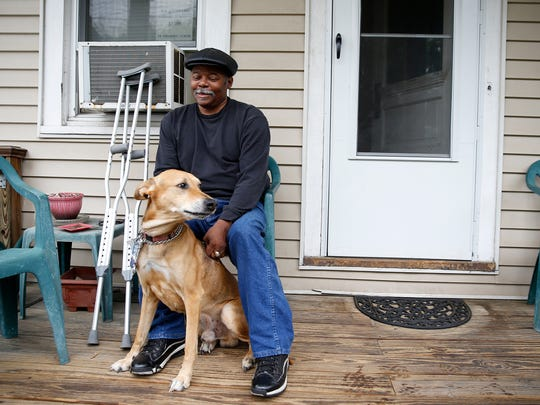 Kenneth Starks sits with his dog Romeo at his home