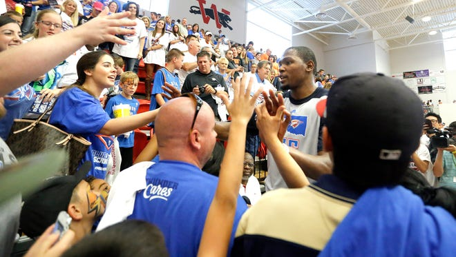 Kevin Durant greets fans after the Thunder's scrimmage at Westmoore High School in Moore, Okla., on Sunday, in an effort for tornado relief.