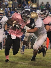 Milan's Spencer Walker (1) runs the ball as Huntingdon's (76) moves in for the tackle on Friday night.