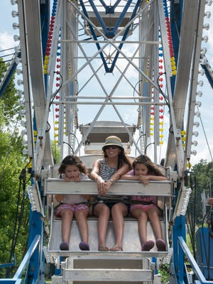 Elena Jones takes twin daughters Isabella and Natalia for a spin on the Ferris wheel at last year's Sourwood Festival.