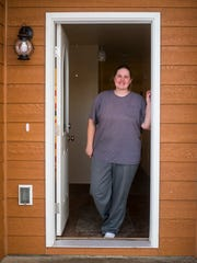 Alissa Doland stands in the doorway of her home. She and Jazmyn coincidentally chose the same floor layout and exterior colors for their next-door houses.