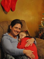"""Joan Walleser holds her daughter Kylie Walleser-Bush on Thursday while she sleeps. The 9-year-old will fall asleep for hours during the day, often at school, as """"her little body gets tired"""" of functioning and can't go anymore, Walleser said. Kylie Bush was born with short gut syndrome and is in need of a small intestine, liver and pancreas transplant."""