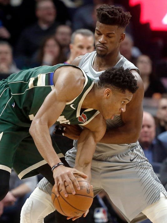 Milwaukee Bucks' Giannis Antetokounmpo, left, of Greece, assumes a low profile as he drives around Minnesota Timberwolves' Jimmy Butler in the first half of an NBA basketball game Thursday, Feb. 1, 2018, in Minneapolis. (AP Photo/Jim Mone)