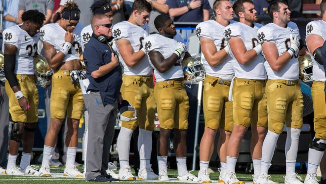 Sep 16, 2017; Chestnut Hill, MA, USA; Notre Dame Fighting Irish head coach Brian Kelly and his players stand for the national anthem before the game against the Boston College Eagles at Alumni Stadium. Mandatory Credit: Matt Cashore-USA TODAY Sports