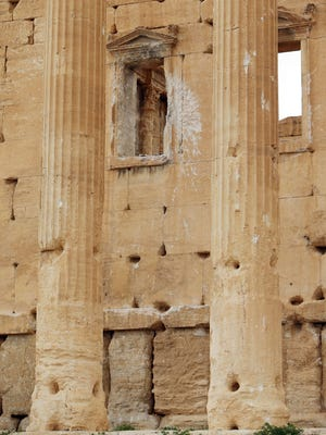 A file picture taken on March 14, 2014, shows damage caused by shelling on a wall in the ancient oasis city of Palmyra, Syria.