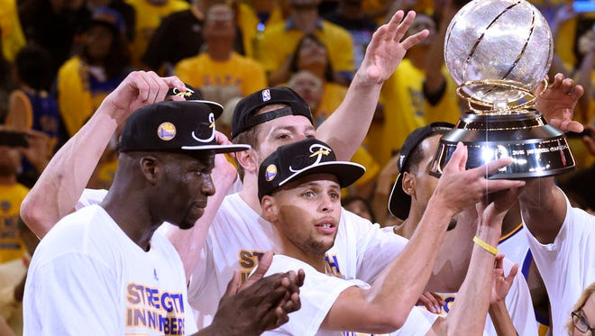Golden State Warriors guard Stephen Curry (30) celebrates with the western conference championship trophy after defeating the Houston Rockets in game five of the Western Conference Finals of the NBA Playoffs at Oracle Arena.