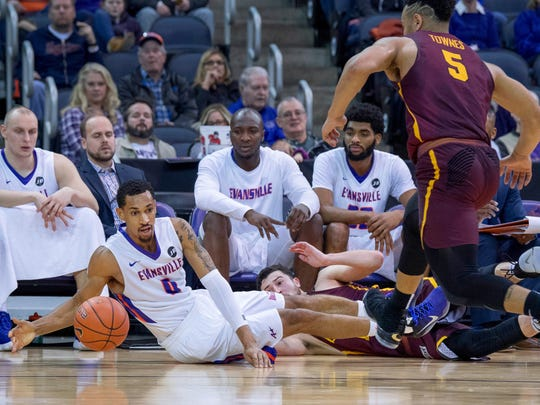 Evansville's Ryan Taylor (0) loses the ball on the sidelines while be defended by Loyola Chicago's Marques Townes (5) and Ben Richardson at the Ford Center Sunday afternoon. Loyola beat Evansville 76-66.