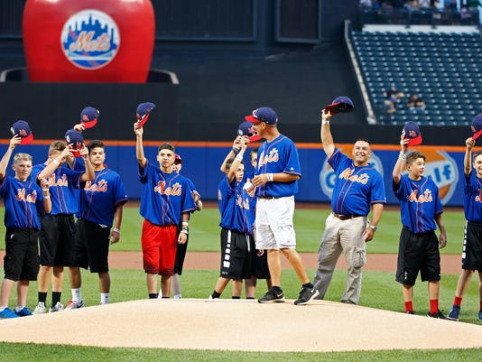 Members of the Maine-Endwell Little League World Series championship team tip their caps as their manager, Scott Rush, center, prepares to throw out the ceremonial first pitch before a baseball game between the New York Mets and the Miami Marlins, Wednesday, Aug. 31, 2016, in New York. (AP Photo/Kathy Willens)