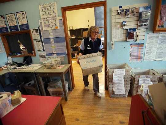 Marj Hendershot carries a mail bin Monday through the post office on Pacific Avenue in Bremerton.