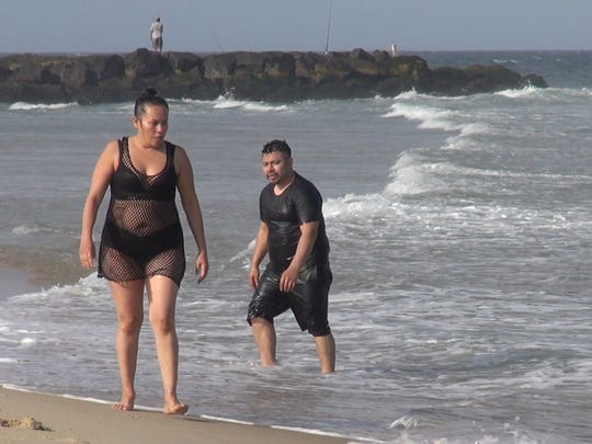 Manny Ixcampary of Elizabeth and his wife head back out of the water after a cool swim late at night.