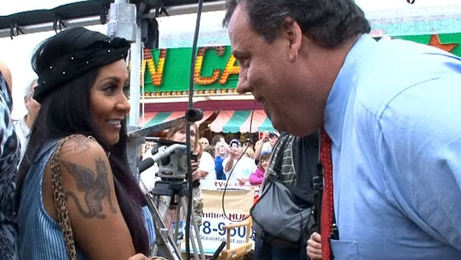 "New Jersey Governor Chris Christie leans in on  MTV ""Jersey Shore"" cast member Nicole ""Snooki"" Polizzi after they met up Friday morning on the Seaside Heights, NJ, boardwalk after appearances on the ""Today"" show in May, 2013."