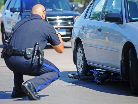 A Sioux Falls Police officer photographs a mangled bicycle underneath a car after a bicycle versus car accident on Wednesday, July 23, 2014, near the corner of 41st Street and Larch Avenue in Sioux Falls, S.D.