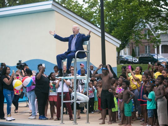 Former Vice President Joe Biden sits in the lifeguard chair and cheers along with the crowd as they reveal the renaming of the pool facility being dedicated in his honor to the Joseph R. Biden Jr. Aquatic Center in Wilmington, Del.