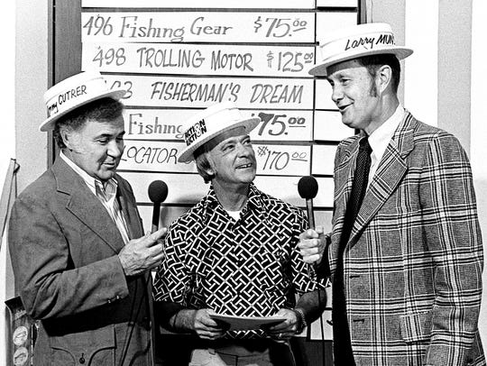 Jimmy Holt, center, tells emcee T. Tommy Cutrer, left, and Larry Munson all about the fishing trip he is planning for a lucky Action Auction bidder during the fundraiser for WDCN-TV public television April 18, 1974. Munson was to join Holt and the winner on the fishing trip.