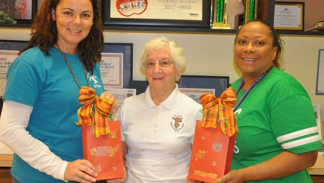 El-Doe Vice President Bernice Shoffner-May, center, presents the $75 gift cards to Natasha Steenburgen, left, behavior intervention specialist, and Letitia Hart, principal at Sebastian Elementary School.