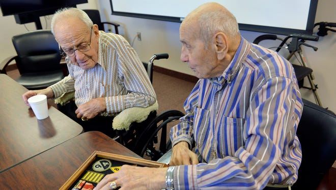 Wally Pfuhl, right, 99, and brother, Clarence, 100, reminisce over some of Wally's World War II patches and medals Oct. 15 at St. Benedict's Senior Community.