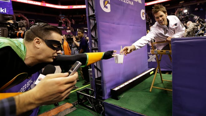 A reporter from Nickelodeon gives New England Patriots' Tom Brady noodles with chop sicks during media day for NFL Super Bowl XLIX football game Tuesday, Jan. 27, 2015, in Phoenix. (AP Photo/Mark Humphrey)