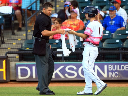 Hooks' batboy Noah Garcia hands a towel to home plate umpire Justin Robinson on Saturday, July 8, 2017, at Whataburger Field in Corpus Christi. Noah, who is one of 35 students nationwide to be named a Catholic Life Insurance All-American Scholar, says he has never missed a Sunday or holy day of obligation Mass.