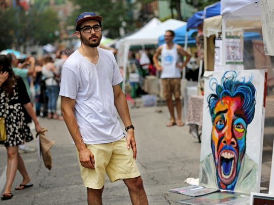 Norwin Adarve, 19, in front of his booth at Second Sunday on Main in Over-the-Rhine.