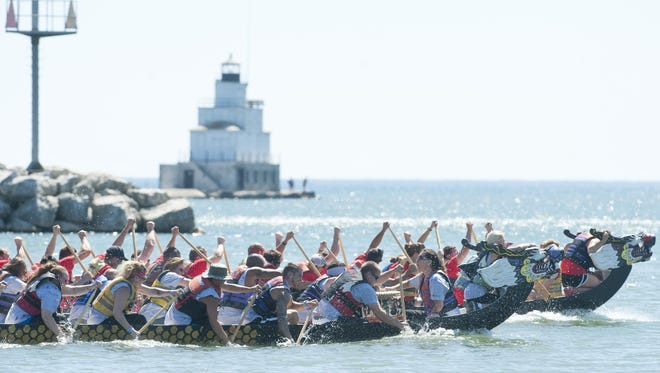 Team Federal-Mogul, front, and team TJ's Sports Bar & Grill and Shoreline Dental compete against each other in dragon boat racing during the Lakeshore Weekend at YMCA on Saturday, Aug. 1 in Manitowoc. It was the 25th anniversary of the Lakeshore Weekend event and the 20th year of dragon boat racing.