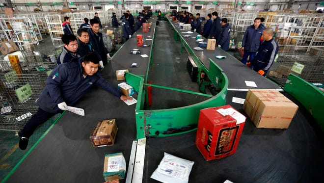 Workers sort out parcels at a sorting center of an express delivery company Monday, one day ahead of the online shopping festival  in Beijing known as Singles' Day.