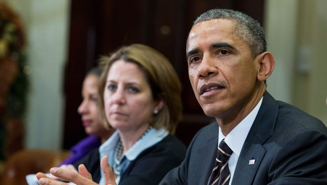 White House Homeland Security Advisor Lisa Monaco sits beside President Obama during a meeting with his national security and public health teams Dec.12, 2014.